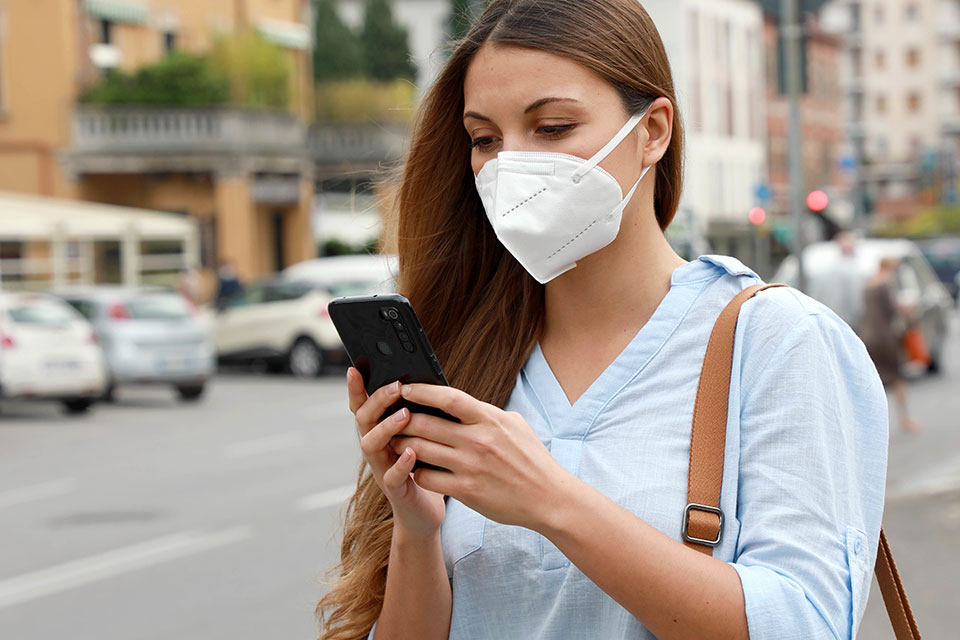 Woman in Mask Using Cell Phone