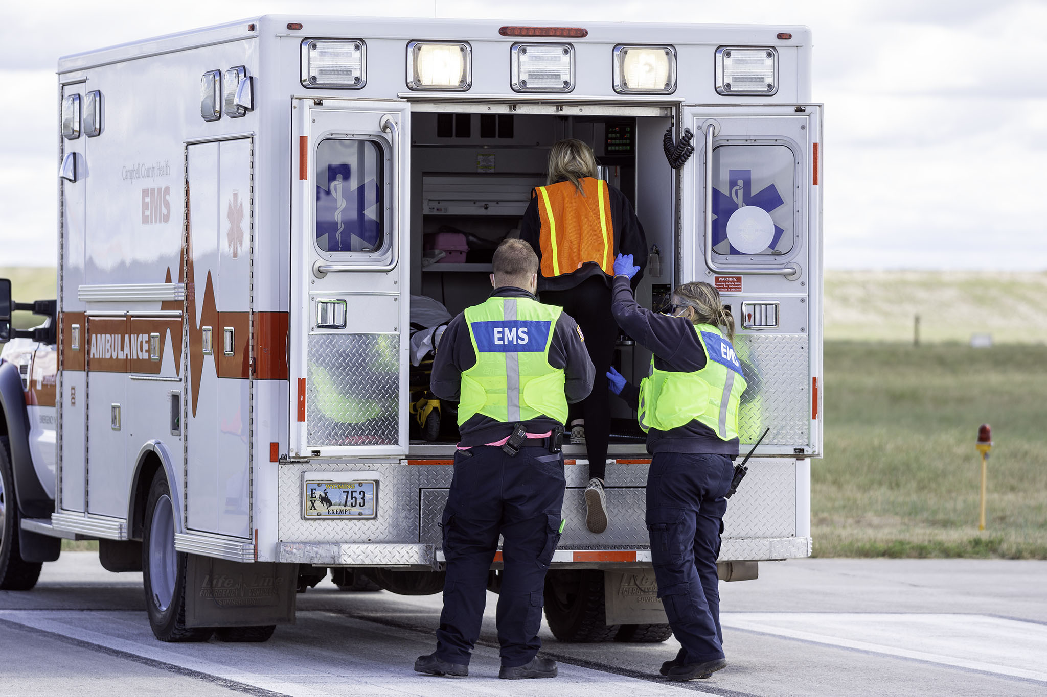 Two EMS personnel help a victim into the ambulance