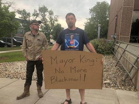Jeff Rainey holds a sign stating,