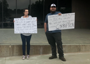 Gillette husband and wife, Renee Cunningham and Mason Edwards, hold signs outside of Tuesday's City Council meeting