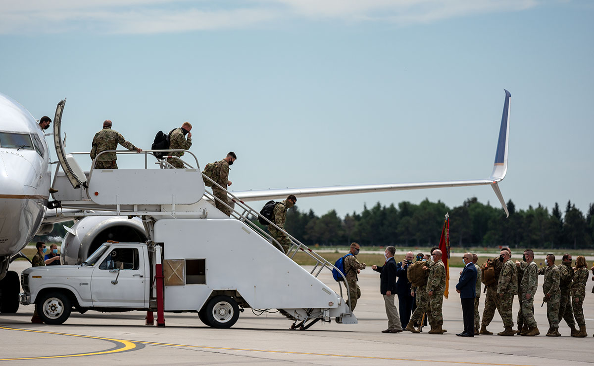 Soldiers of the 115th Field Artillery Brigade exit off the plane.