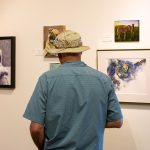 """A gentleman browses the gallery of artwork featured as """"Man's Best Friend."""""""