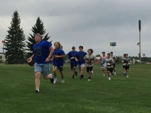 Fooball players warm up with two laps around the practice field.
