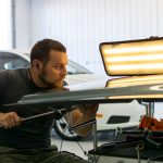 Michael Bowers, PDR Tech, works on removing dents from the hood of a vehicle.
