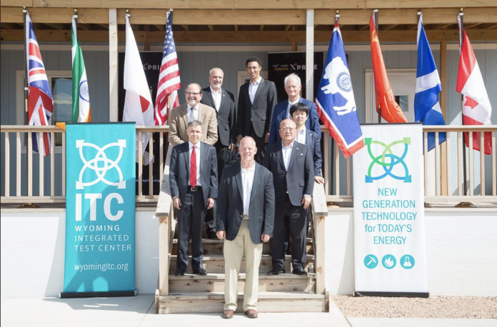Wyoming Integrated Test Center (ITC) supporters, including former-Gov. Matt Mead, Sr. Carbon XPRIZE Dir. Marious Extavour and Japan Coal Energy Center Pres. Osamu Tsukamoto, among others, stand at the doors of the ITC during a dedication ceremony in May 2018. (H/t ITC)