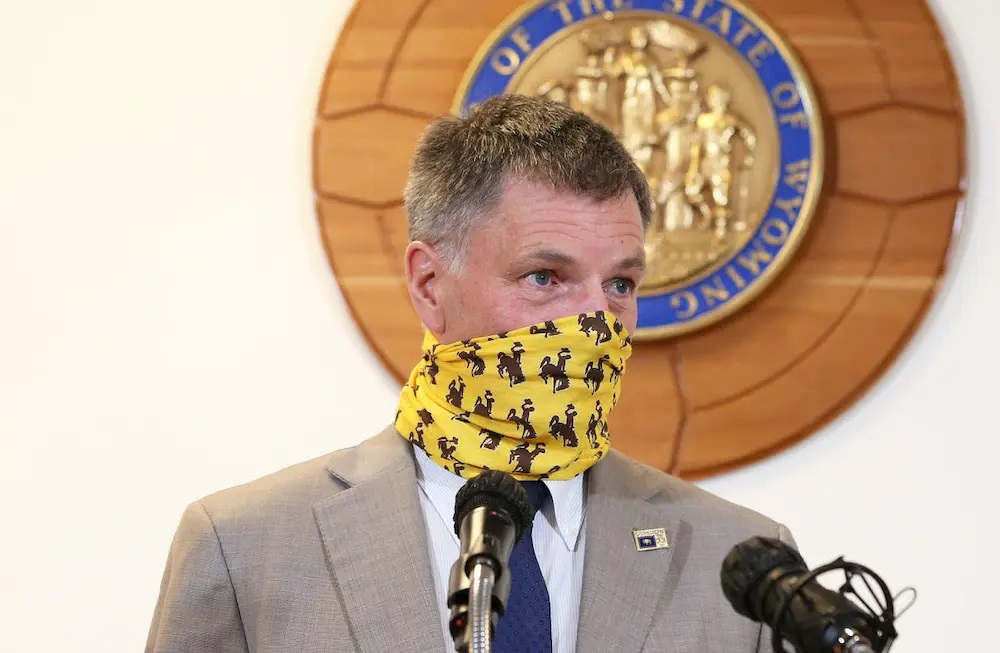 Gov. Mark Gordon wears a University of Wyoming face covering before pulling it down to begin a media briefing Wednesday, May 20, 2020, inside the Capitol. (Michael Cummo/Wyoming Tribune Eagle/Wyoming News Exchange)