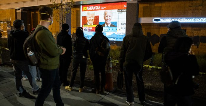 Protesters watch the U.S. presidential election results roll in Nov. 3 near the White House in Washington. Democratic nominee Joe Biden is favored to win, but thousands of votes in key states have not yet been tallied. (Photo courtesy of Francis Chung/E&E News, Used Under License)