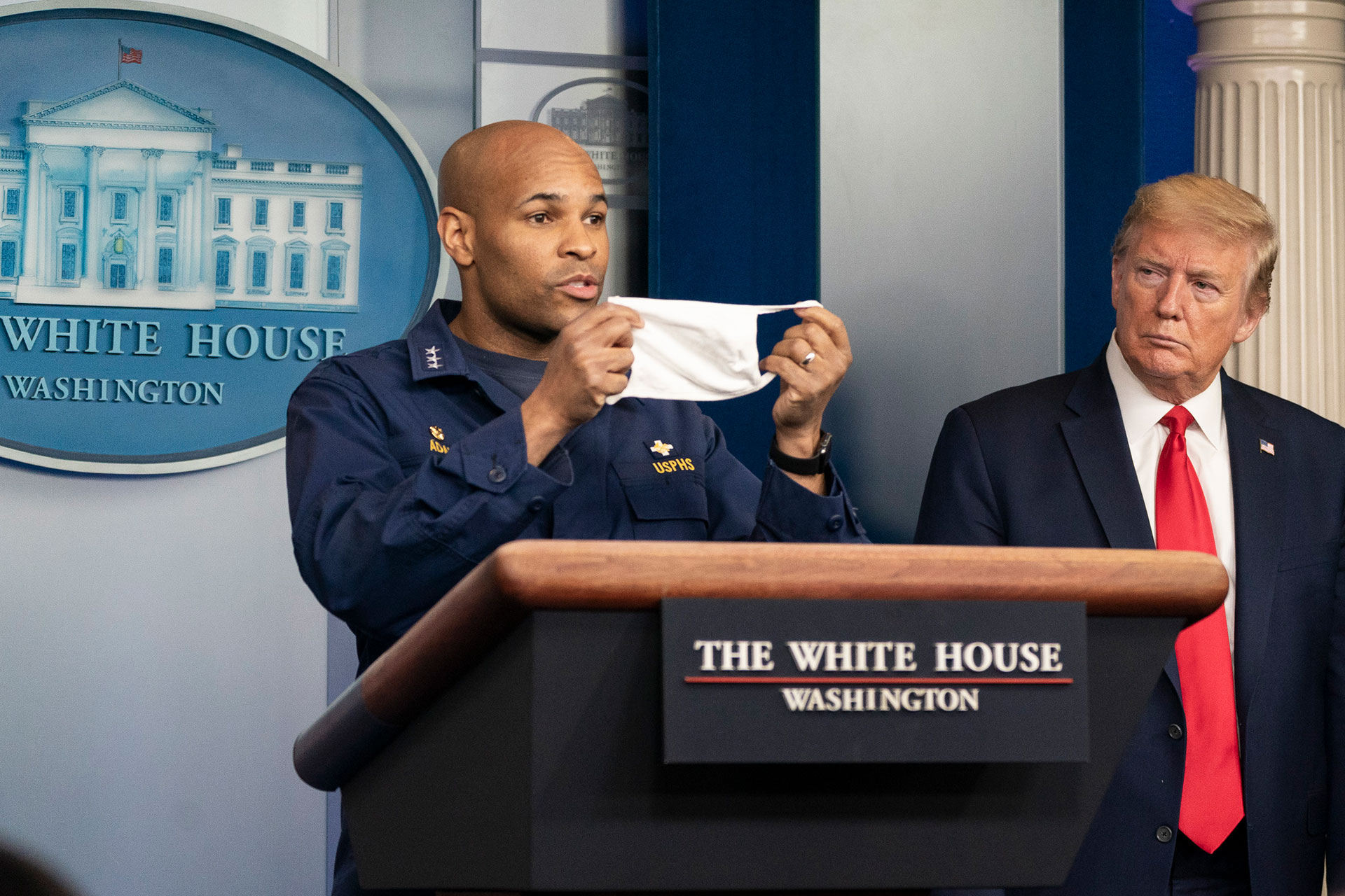 President Donald J. Trump listens as U.S. Surgeon General Jerome Adams delivers remarks and urges citizens to wear masks in public at the coronavirus (COVID-19) update briefing Wednesday, April 22, 2020. (Official White House Photo by Shealah Craighead, Flickr/Public Domain)