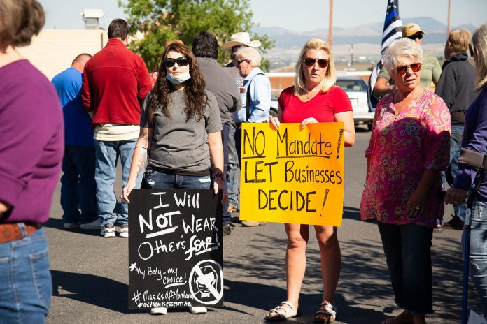 Protesters hold signs protesting mask mandate in the health department parking lot (Helena, Montana, September 11, 2020) (Used under License).
