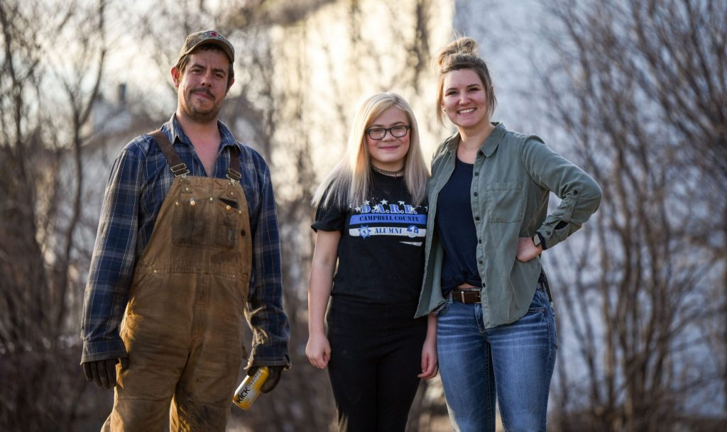 Kierra Bulkley (right) hired Callie to clean up her front yard and dad Fennis helped her get the job done Wednesday.