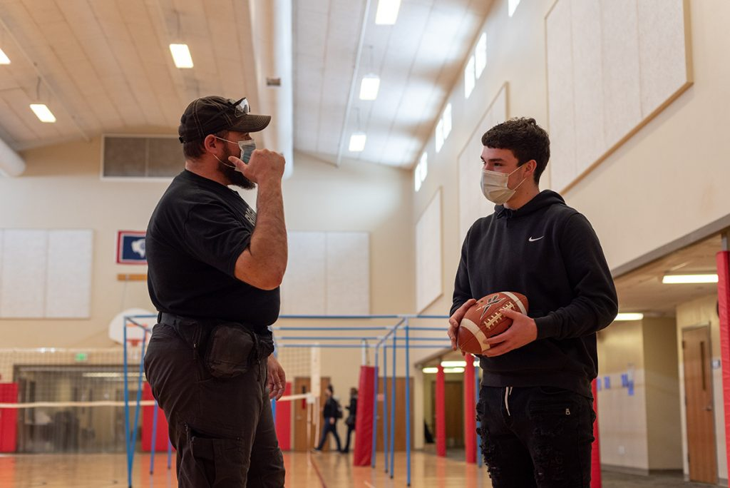 GPD officer Zach Parker confers with his mentee, Braydon Meyer, between football tosses at the Y.E.S. House Tuesday.