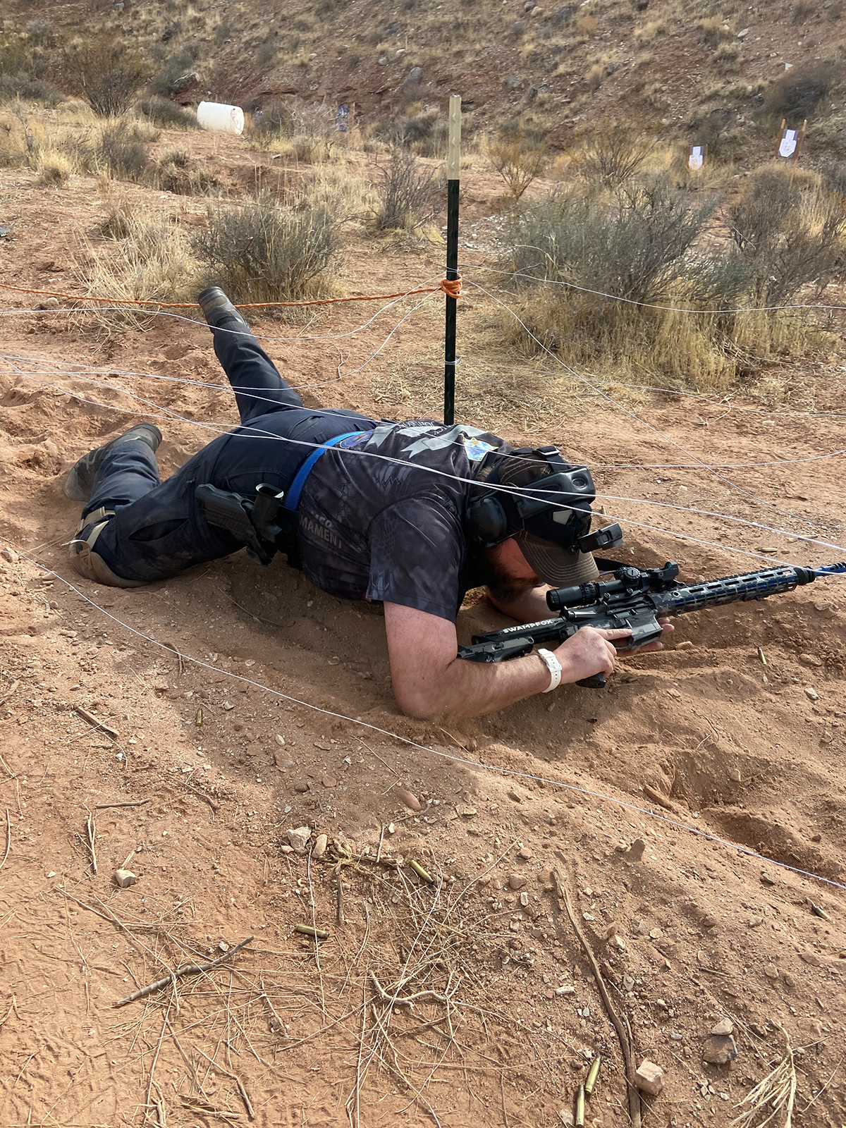 Gillette Police Department Officer, Zachary Parker, army crawls under wires and through dirt to get to his next shooting target. (Photo: Zachary Parker)