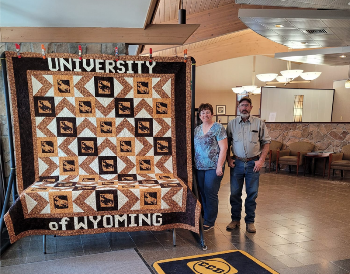 Campbell County residents and long-time 4-H supporters Kathy and Russell Bell stand beside a handmade quilt available for raffle through Extension offices across the state. (Photo: Courtesy Kathy Bell)